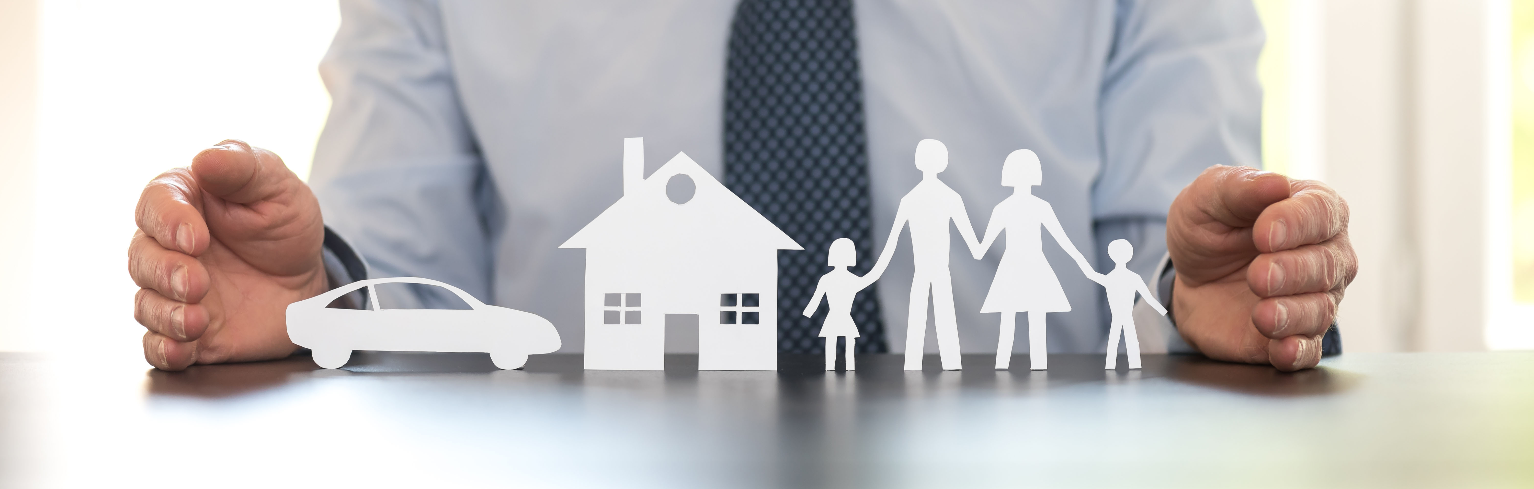 photo of a person holding out a paper cutout of a family, a house and a car