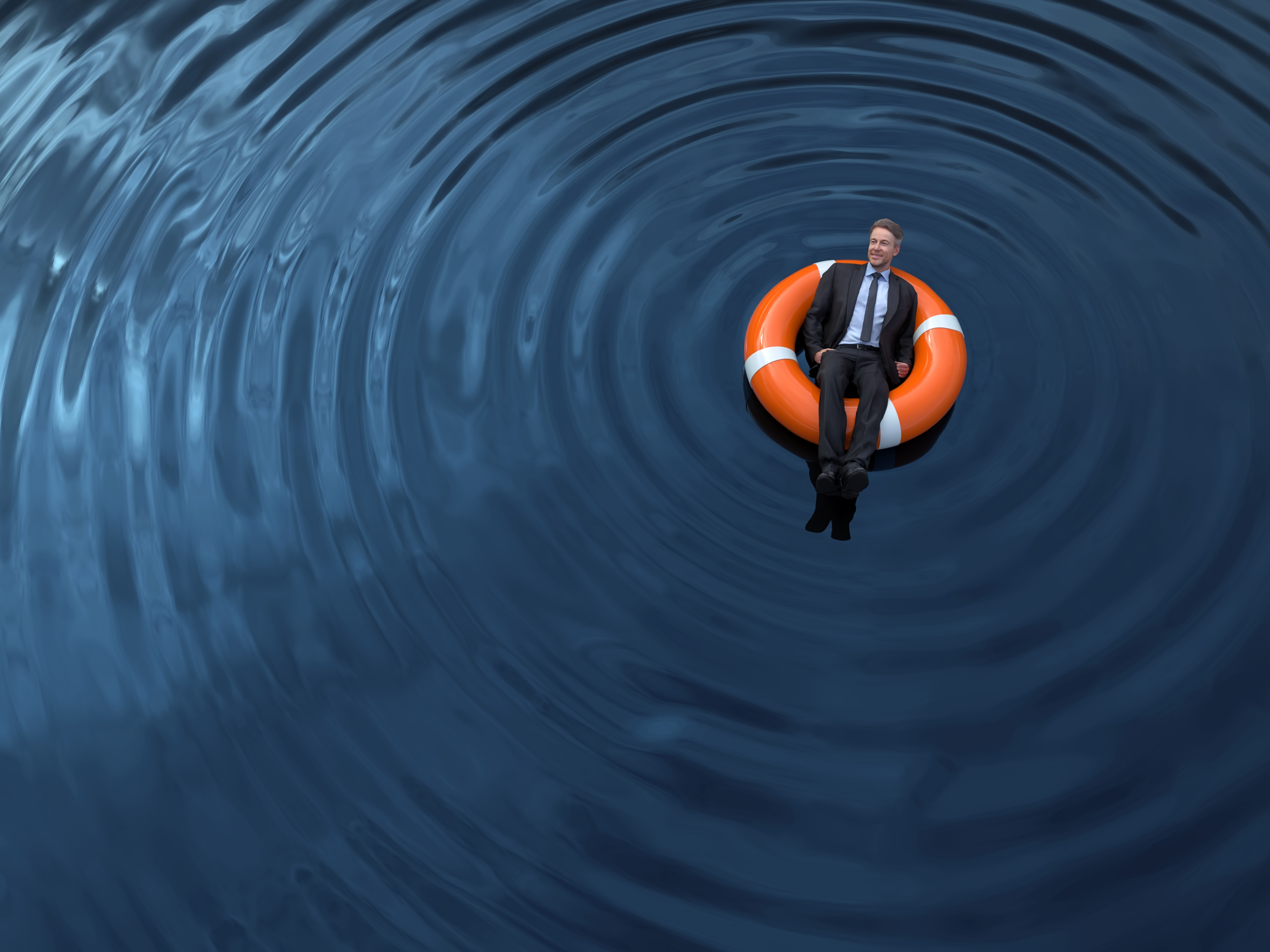 man in a suit lounging in an orange innertube in the middle of a body of water