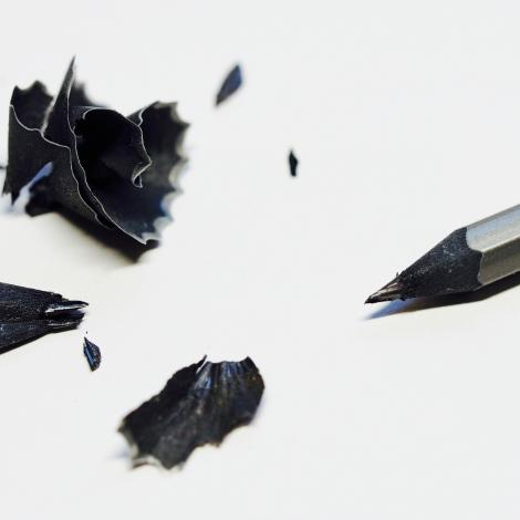 photo of a sharpened grey pencil with its pencil shavings next to it