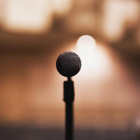 photo of a microphone facing the camera as if the camera man is going to use it there are blurred stage lights in the background