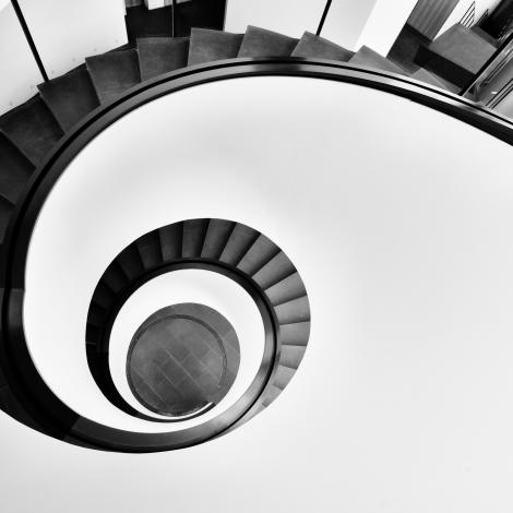 photo of the top of a black spiral staircase contrasted to a white wall around it