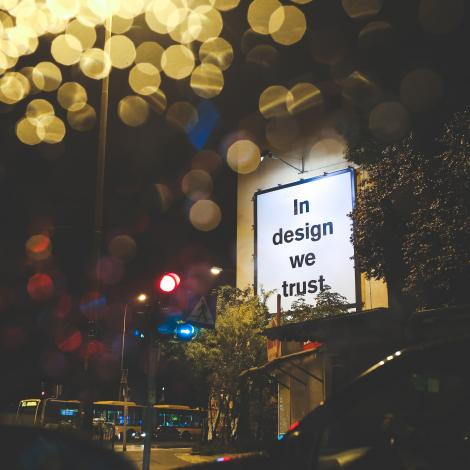 "photo of a lit billboard that says ""in design we trust"""