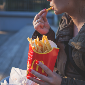 a person eating french fries from a mcdonald's fry carton