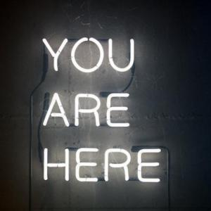 a white neon sign that reads 'you are here'