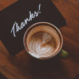 "photo some two hands cradling a coffee cup, there's a text overlay that reads ""thanks!"""