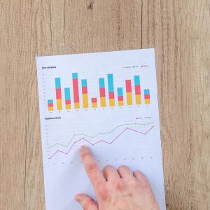 hand pointing at paper with statistics