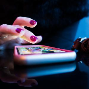 photo of a person with painted nails tapping on a phone