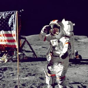an astronaut on the moon next to the american flag. they're saluting the flag next to them