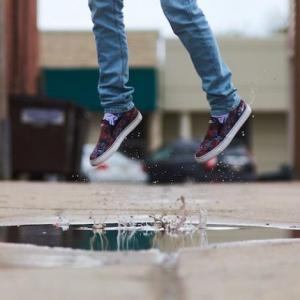 a person in jeans and black tennis shoes jumping in the air above a puddle of water making a splash